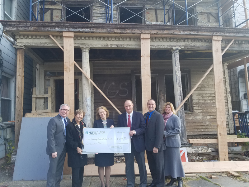 From left, Richard Haggerty, HGAR CEO; Ann Garti, HGAR COO; Kim Jacobs, executive director, Community Capital New York; Ron Garafalo and Cindy Schweizer, HGAR Board members present check to Community Capital outside of a property slated for rehab in the City of Newburgh.